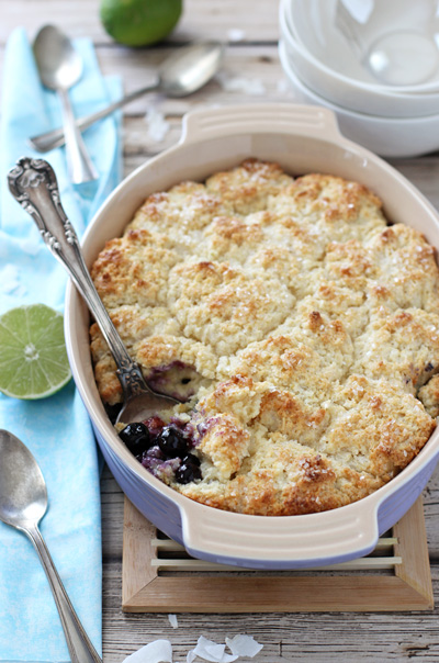 A purple baking dish filled with Blueberry Lime Coconut Cobbler.