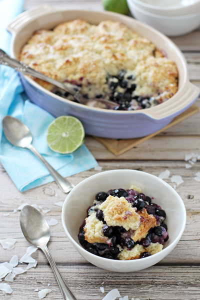 A white bowl with a serving of Blueberry Lime Cobbler with the baking dish in the background.