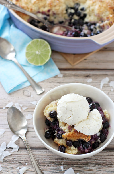A white bowl with Blueberry Coconut Cobbler topped with vanilla ice cream.