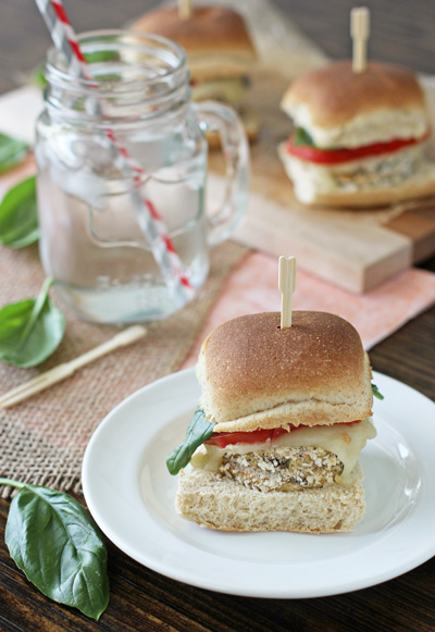 An Eggplant Slider on a white plate with a glass of water to the side.