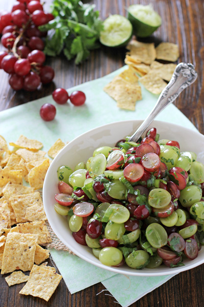 A white bowl filled with Grape Salsa and chips to the side.