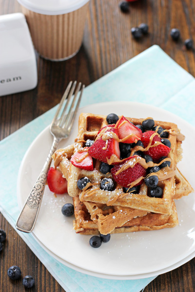 Several Almond Butter Waffles on a white plate drizzled with more almond butter and berries.