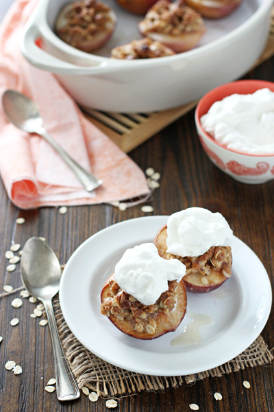 Two Baked Peaches with whipped cream on a white plate.