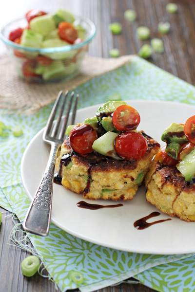 Two Healthy Corn Fritters on a white plate with a fork.