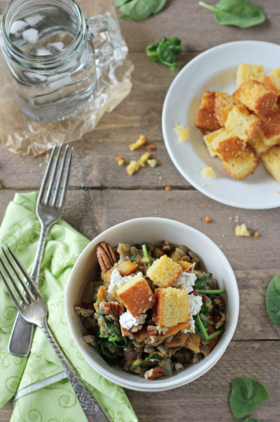 A white bowl filled with Fall Lentil Salad and a plate of cornbread croutons.
