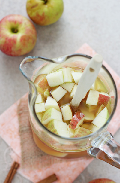 A glass pitcher filled with Fall Sangria with fresh chopped apples.