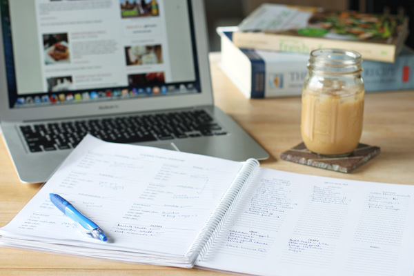 A laptop, notebook and iced latte on a wooden table.
