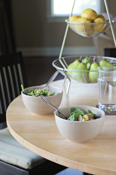 Two bowls of salad and a glass of water on a kitchen table.