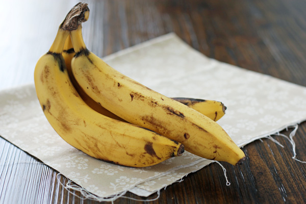 Several bananas on a wooden table.