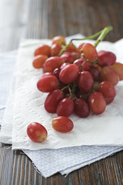 A bunch of red grapes on a wooden table.