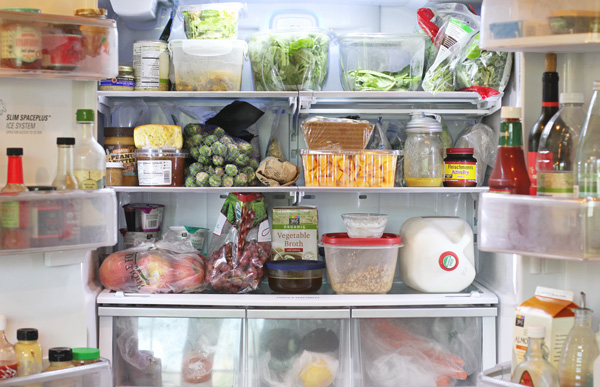 An open fridge stocked with lots of groceries.