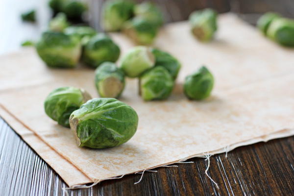 Several fresh brussels sprouts scattered on a wooden table.