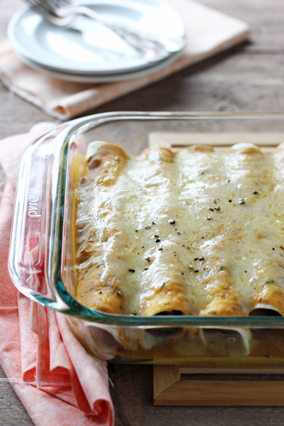 A glass baking dish with Sausage Enchiladas and plates in the background.