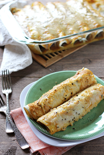 Two Fall Enchiladas on a green plate with the baking dish in the background.