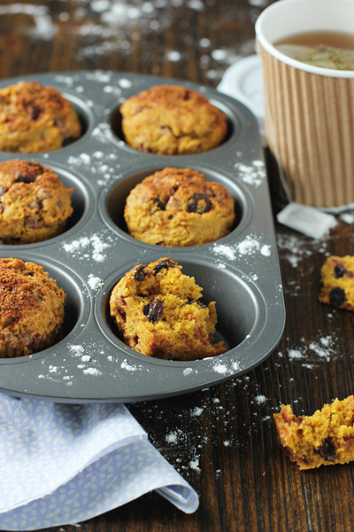 Chocolate Chip Pumpkin Muffins in a muffin tin with one split in half.