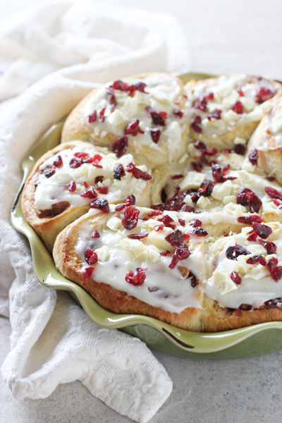 A pie dish filled with Cranberry Cinnamon Rolls and a white napkin to the side.