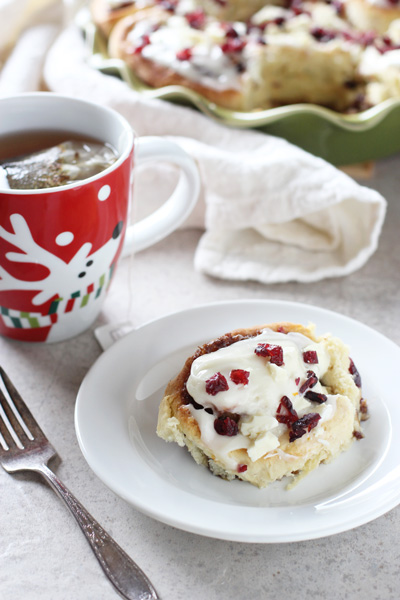 A Cranberry Bliss Cinnamon Roll on a white plate with a cup of tea to the side.