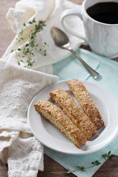 Three Lemon Thyme Biscotti on a white plate with coffee in the background.
