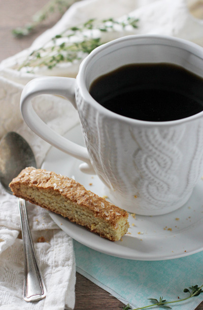 A cup of coffee with a partially eaten Lemon Thyme Biscotti on the saucer.