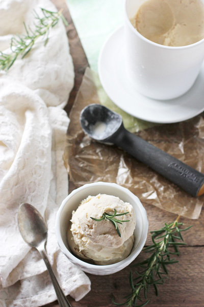 Homemade Rosemary Ice Cream in a white bowl with a pint to the side.