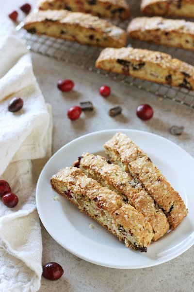 Three Fresh Cranberry Biscotti on a white plate with more in the background.