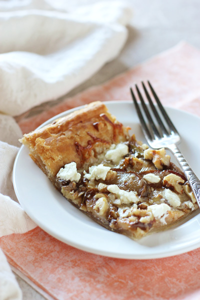 An easy appetizer recipe for pear, walnut and goat cheese tart. With a puff pastry crust and topped with caramelized pears, cheese and nuts!