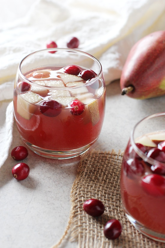 Two glasses of Champagne Sangria with fresh cranberries scattered around.