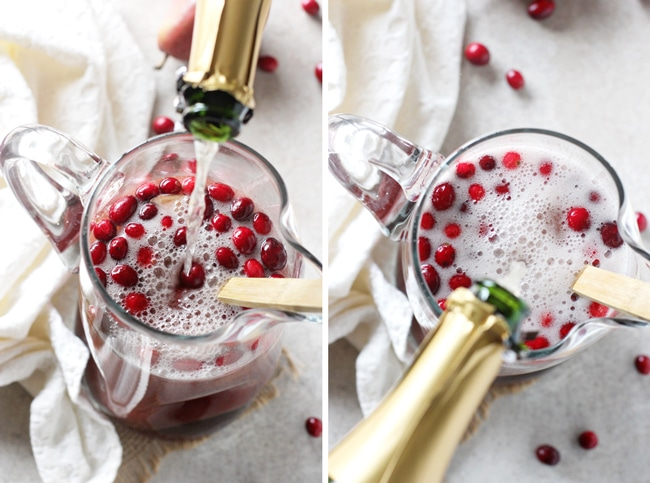 A glass pitcher filled with Winter Sangria and someone pouring in a bottle of champagne.