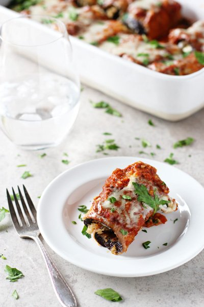 A white plate with one Sweet Potato Eggplant Rollatini with a baking dish in the background.