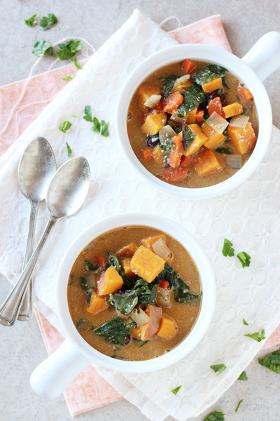 Two white bowls filled with Creamy Sweet Potato Swiss Chard Soup.