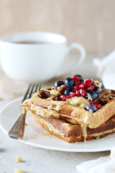 A white plate with two Banana Peanut Butter Waffles and a cup of tea.