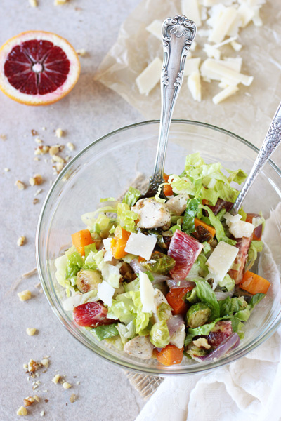 A glass mixing bowl filled with Winter Chopped Salad.