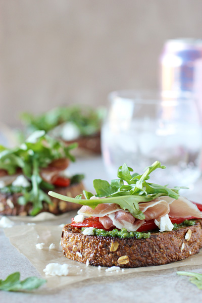 Several Open Faced Sandwiches on parchment paper with sparkling water in the background.