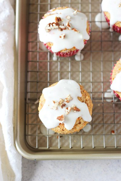 Several Healthy Carrot Cake Muffins on a wire rack set instead a baking pan.
