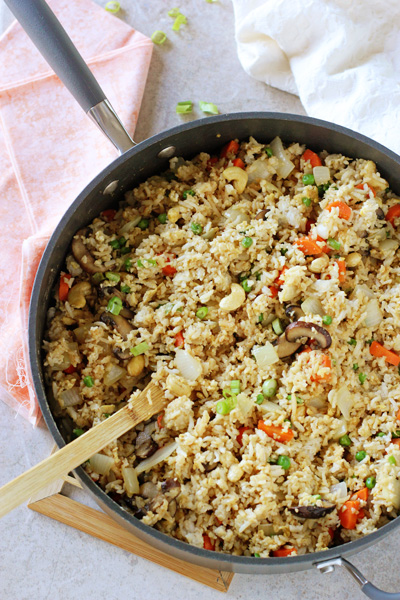 A skillet filled with Healthy Vegetable Fried Rice with a wooden spoon in the dish.