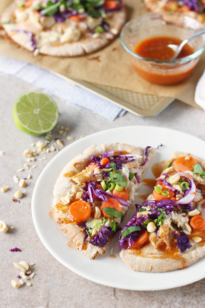 Recipe for 30-minute thai chicken pita pizzas. With shredded chicken, crunchy veggies and a sweet and spicy sauce for drizzling. Perfect for a weeknight!