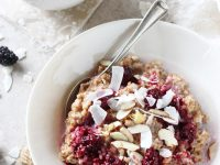 Recipe for creamy blackberry coconut bulgur breakfast bowl. With whole grain bulgur as the base and topped with a blackberry sauce, coconut and nuts!