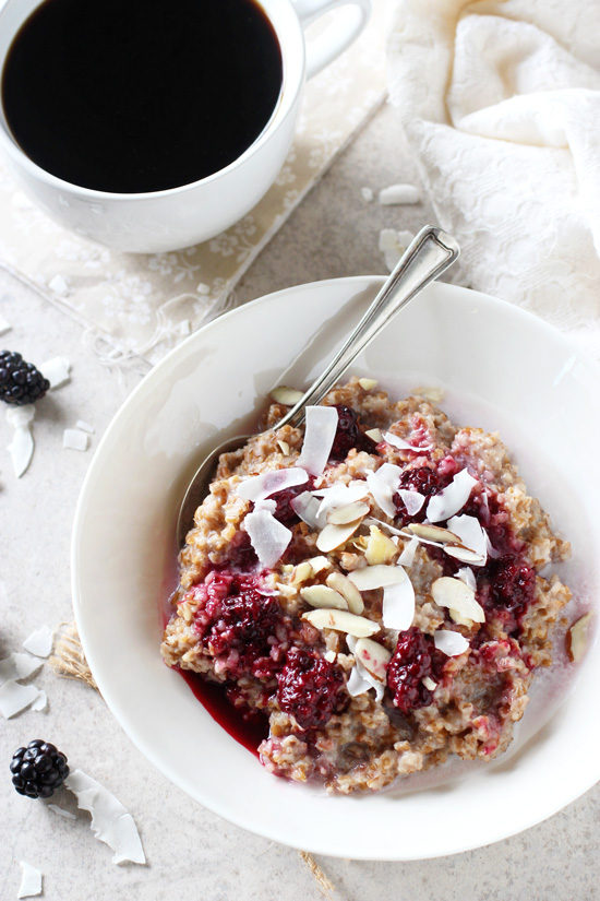 Recipe for a creamy blackberry coconut bulgur breakfast bowl. With whole grain bulgur as the base and topped with a blackberry sauce, coconut and nuts!