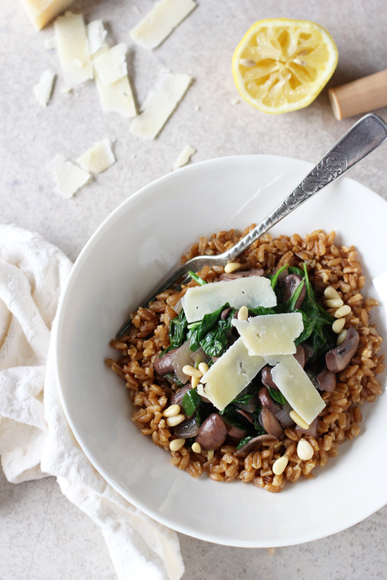 A white bowl filled with Lemon Garlic Farro with a fork in the dish.