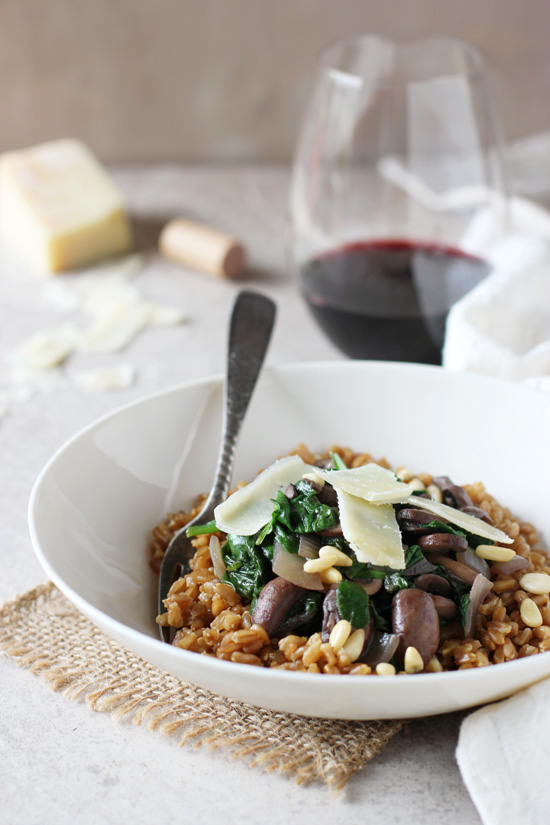 A white bowl filled with Lemon Farro and sautéed mushrooms and spinach.