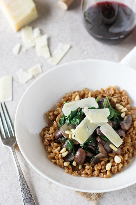 A white bowl full of Farro With Mushrooms and a glass of wine to the side.