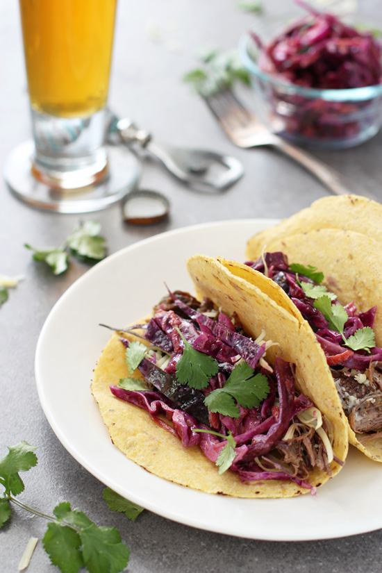 Recipe for slow cooker garlic beef tacos. Tender short ribs full of flavor and topped with white cheddar and a slightly creamy slaw!