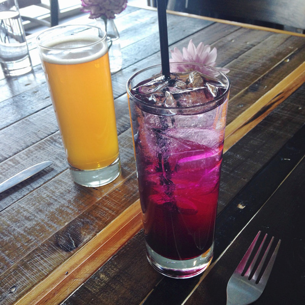 Two cocktails on a wooden table.