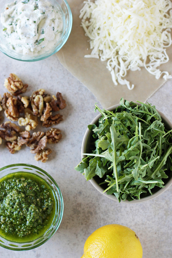 Small bowls filled with arugula, pesto, ricotta, cheese and walnuts.