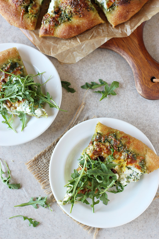 Two slices of Arugula Topped Pizza on white plates with the full pizza in the background.