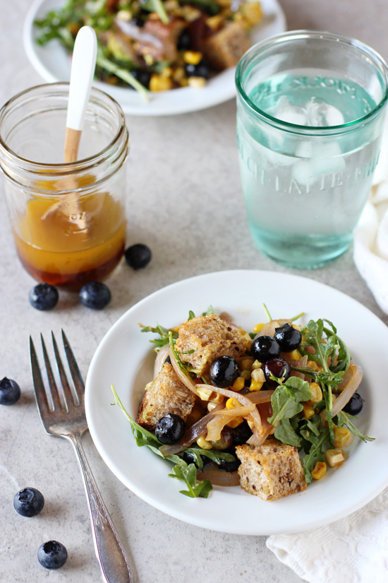 A white plate filled with Blueberry Panzanella with a glass of water and fork.