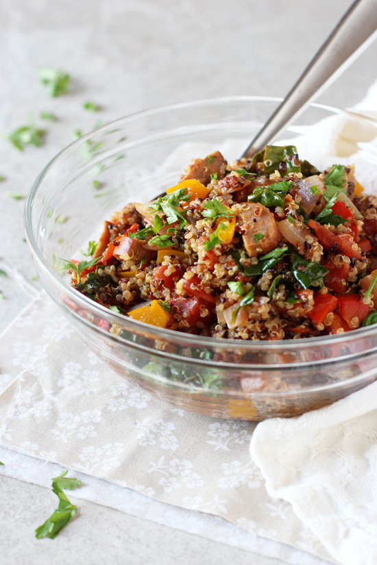 A glass mixing bowl filled with Cajun Quinoa.