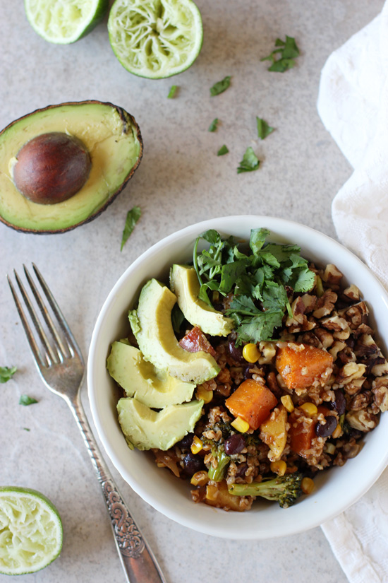 A white dish filled with Mexican Nourish Bowls and an avocado half to the side.