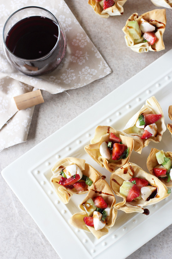 A white platter filled with Strawberry Phyllo Cups and a glass of wine to the side.