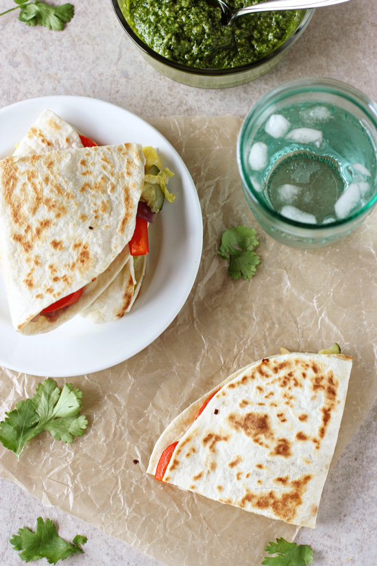 Recipe for weeknight sweet and salty thai vegetable quesadillas. Packed with red pepper, zucchini, cabbage and pineapple! Serve with a homemade cilantro pesto!
